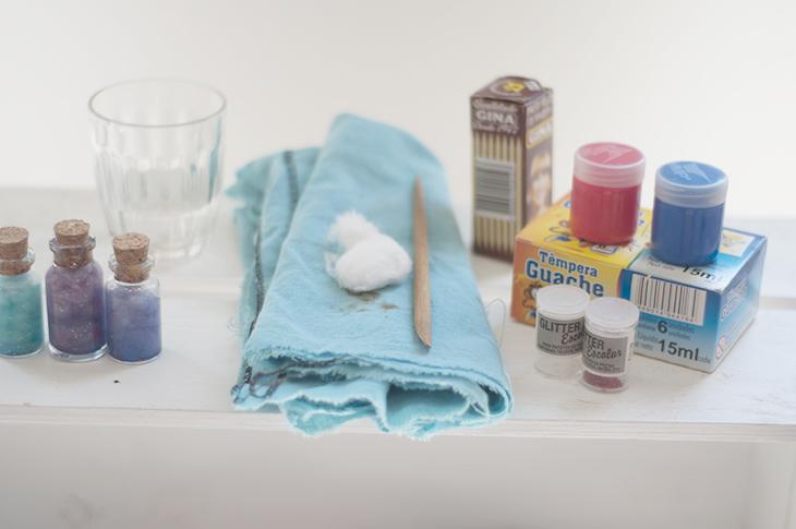 O que você precisa: Tintas, água, garrafa de vidro ou de plástico, glitter e palito.